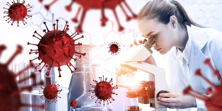 A woman in a white coat looks into a microscope.