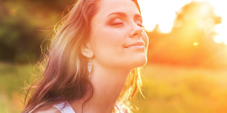 A young woman in the meadow enjoys the sunshine during the sunset
