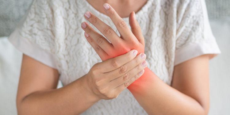 A woman holding a sore wrist.