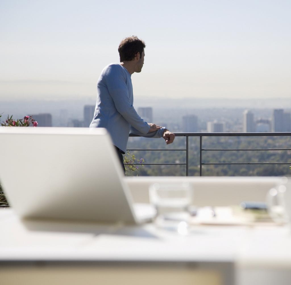A man uses a laptop on a balcony overlooking the city