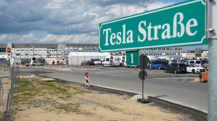 """Das Straßenschild """"Tesla Straße 1"""" steht an der Zufahrt zum Baugelände der Tesla Fabrik. (Quelle: dpa/Jörg Carstensen)"""