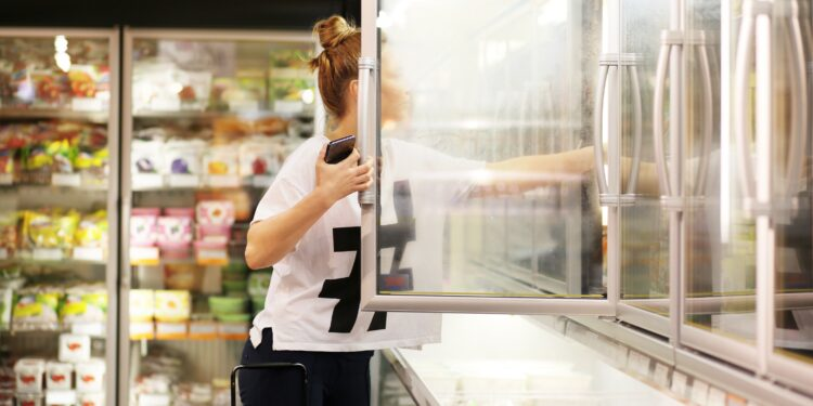 A woman picks out frozen foods from the freezer in the supermarket