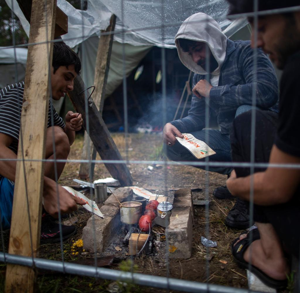 Migrants prepare food at a newly built refugee camp at the Rudninka military training area in Lithuania