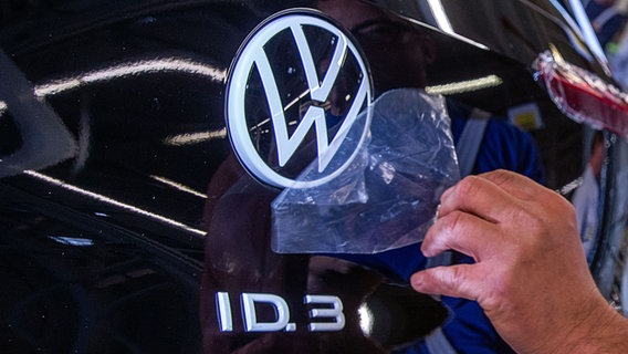 A staff member removes a protective film from the VW logo on the assembly line of the ID.3 electric vehicle production.  © dpa - Bildfunk Photo: Jens Büttner