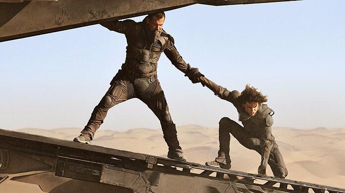 Gurney Halleck (Josh Brolin) helps Prince Paul (Timothée Chalamet) escape from the sandworms.