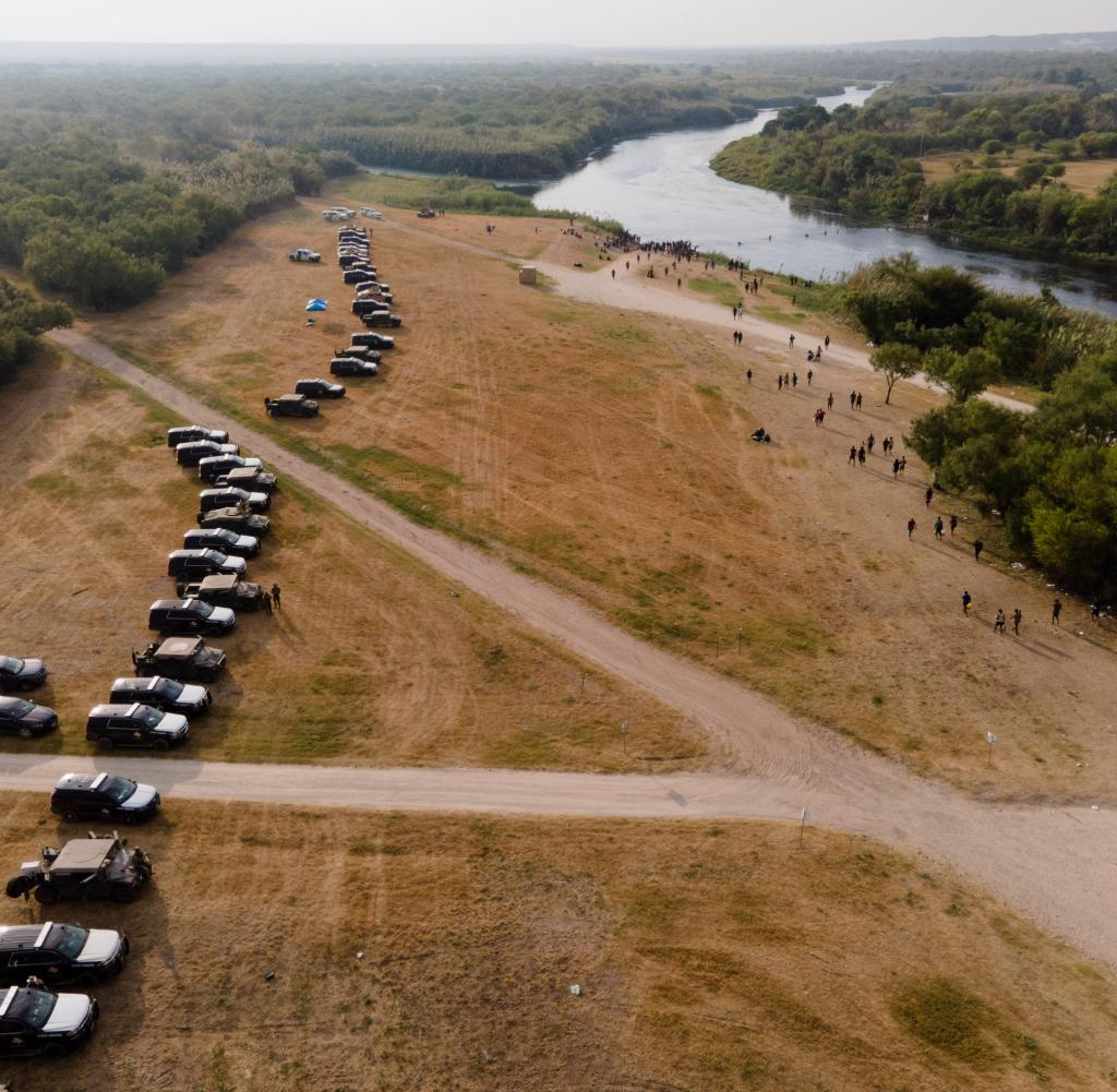 State vehicles line the river border with Mexico, where many immigrants from Haiti are currently waiting