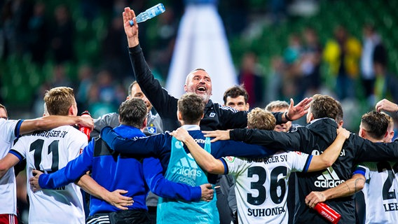 Coach Tim Walter (centre) of Hamburger SV celebrates the 2-0 win over Werder Bremen in the team circuit © IMAGO / Noah Wedel Photo: Noah Wedel